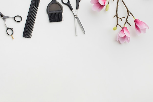 Strumenti per capelli e fiori copiano lo spazio