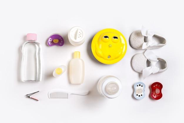 Spazzola per capelli e cosmetici per neonati su uno sfondo bianco vista dall'alto