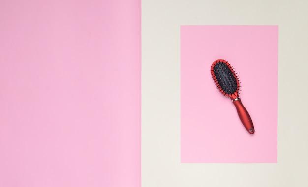 Spazzola per capelli su una superficie pastello rosa. minimalismo. vista dall'alto