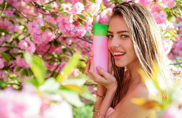 Cura dei capelli, bella donna sorridente con shampoo o balsamo, cosmetici naturali a base di erbe per capelli.