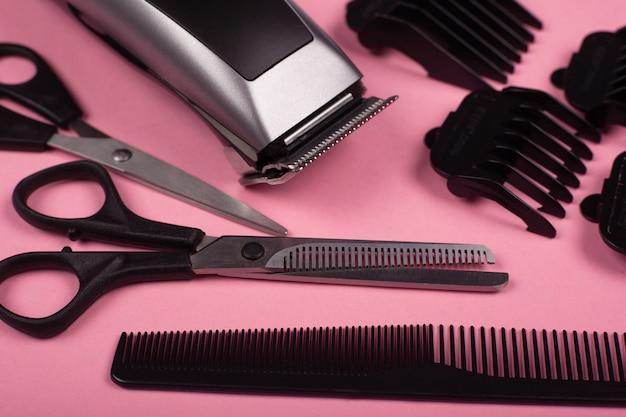 Accessori per il taglio di capelli, strumenti da barbiere su uno sfondo rosa