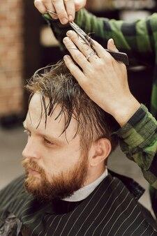 Taglio di capelli nella bottega del barbiere si chiuda