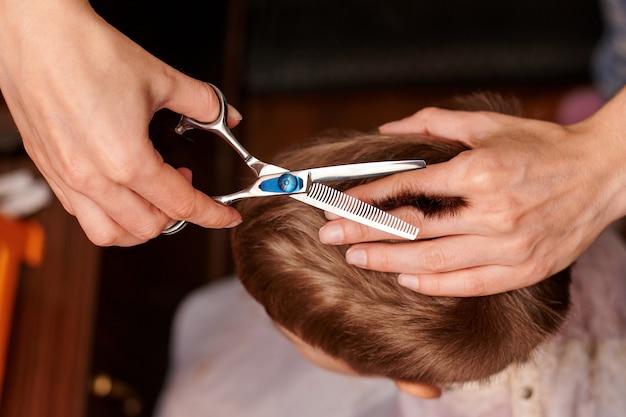 Taglio di capelli di un bambino con i capelli castani.