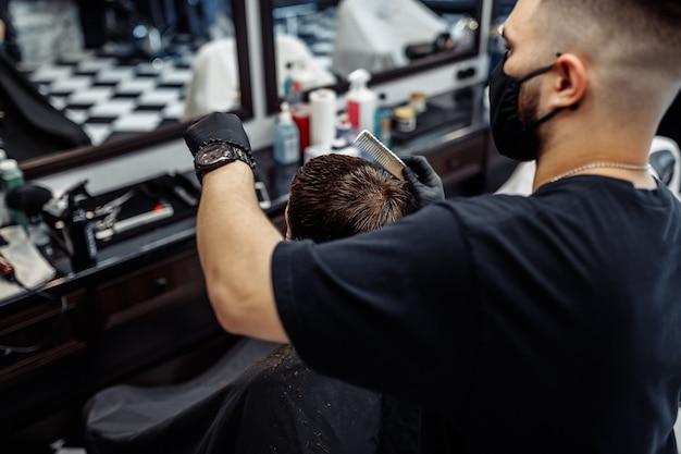 Taglio di capelli in nuove condizioni. novità nel mondo della moda. taglio di capelli maschile in un negozio di barbiere, salone di bellezza.