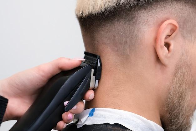 Processo di taglio di capelli di giovane biondo con tagliacapelli in poltrona nel salone del barbiere, concetto di barbiere per uomini e ragazzi