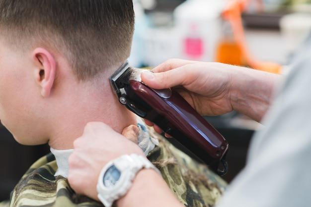 Tagli di capelli dal barbiere. il parrucchiere rade la giovane tosatrice. tagli di capelli da uomo nel salone di bellezza.