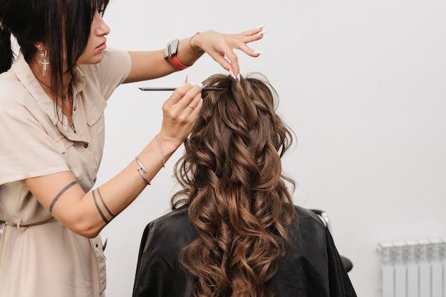 Il parrucchiere in un salone di bellezza fa un'acconciatura per una sposa ragazza con lunghi capelli castani ricci
