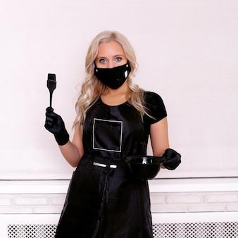 Parrucchiere in abiti professionali neri, maschera e guanti