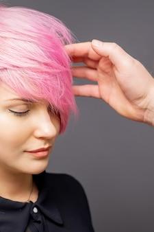Parrucchiere che controlla l'acconciatura rosa della donna.