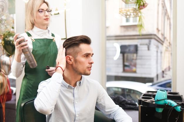 Il parrucchiere e il cliente valutano il risultato dopo il taglio di capelli. stilista facendo acconciatura per ragazzo
