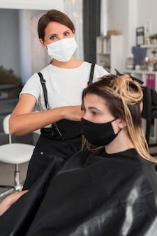 Parrucchiere e cliente che indossa la maschera in tessuto