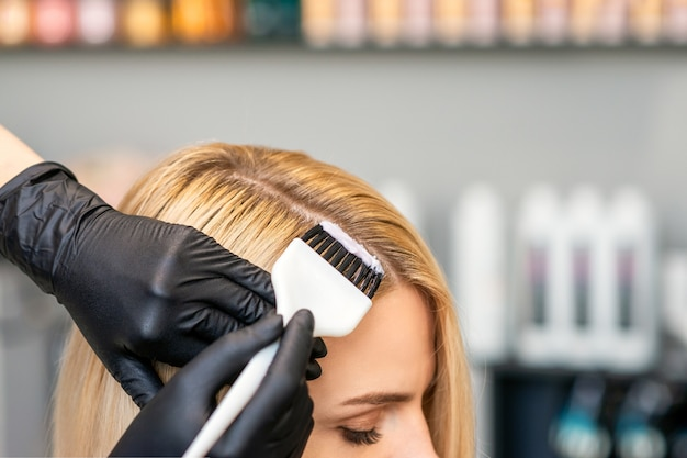 Il parrucchiere colora i capelli delle clienti femminili
