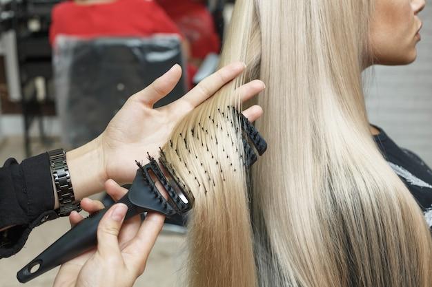 Il parrucchiere pettina i capelli del cliente in stile alla moda. moda donna.