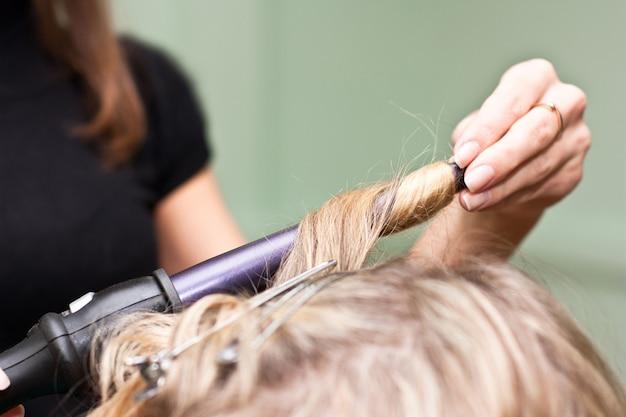 Parrucchiere arricciare i capelli in un salone di bellezza
