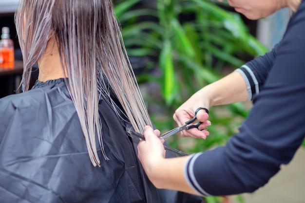 Il parrucchiere taglia i capelli del cliente femminile nel salone di bellezza. servizio clienti dal parrucchiere. fornitura di servizi di taglio dei capelli