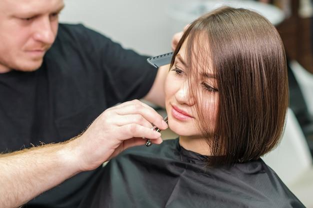 Parrucchiere che taglia i capelli del cliente nel salone di bellezza.
