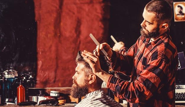 Capelli di taglio del parrucchiere del cliente maschio. cliente che serve parrucchiere al negozio di barbiere. uomo che visita parrucchiere nel negozio di barbiere.