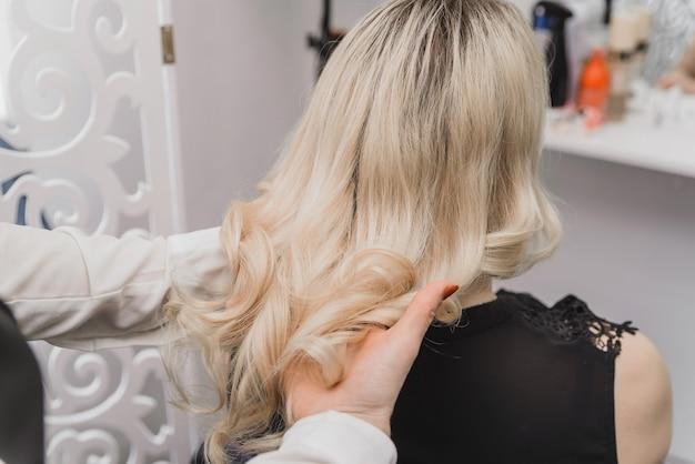 Un parrucchiere fa i capelli di una bionda in un salone di bellezza. fare i riccioli con un ferro arricciacapelli