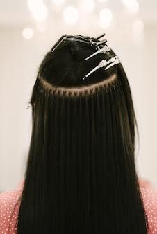 Il parrucchiere fa le estensioni dei capelli a una ragazza in un salone di bellezza