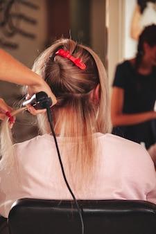 Il parrucchiere fa l'acconciatura carina giovane donna nel salone di bellezza. il servizio clienti nella stanza interna crea un'immagine straordinaria. procedura guidata per la creazione di acconciature da lavoro. concetto di stile di vita sano e benessere