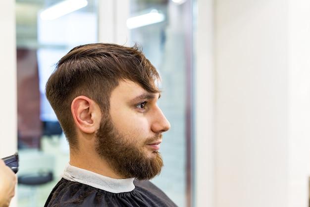 Parrucchiere che fa taglio di capelli per cliente maschio, uomo con la barba utilizzando strumenti professionali di parrucchiere