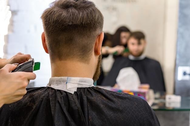 Parrucchiere che fa taglio di capelli per cliente maschio, uomo con barba usando strumenti professionali per parrucchiere,