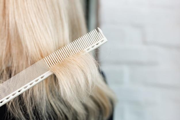 Parrucchiere facendo taglio di capelli parrucchiere professionale forbici pennello sul posto di lavoro per capelli biondi donna