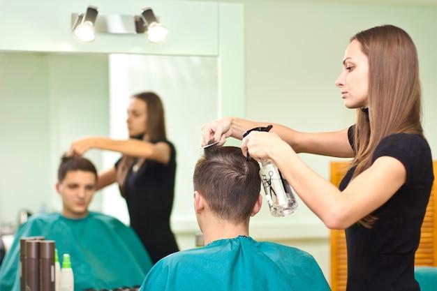 Il parrucchiere asciuga i capelli del ragazzo in un salone di bellezza