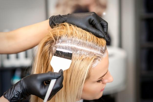 Il parrucchiere che tinge le radici dei capelli biondi con un pennello per una giovane donna in un parrucchiere