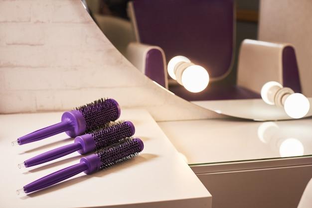 Spazzole per capelli parrucchiere sul tavolo del posto di lavoro
