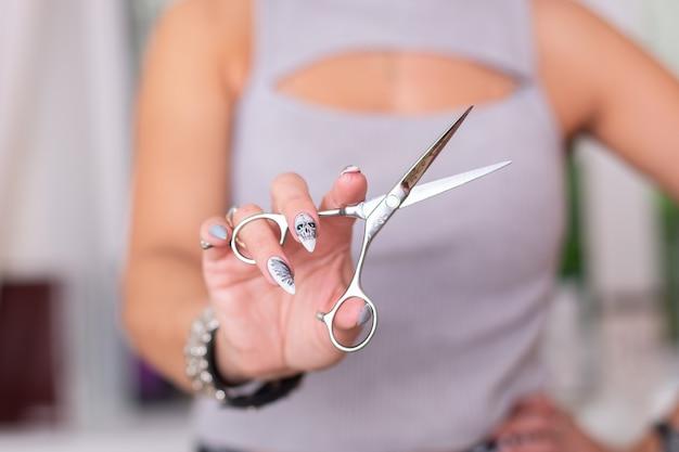 La mano del parrucchiere con le unghie di design di halloween tiene le forbici per il taglio di capelli