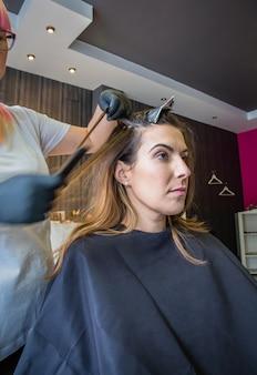 Mani del parrucchiere che pettinano i capelli di bella giovane donna nel processo di cambiamento di colore dei capelli