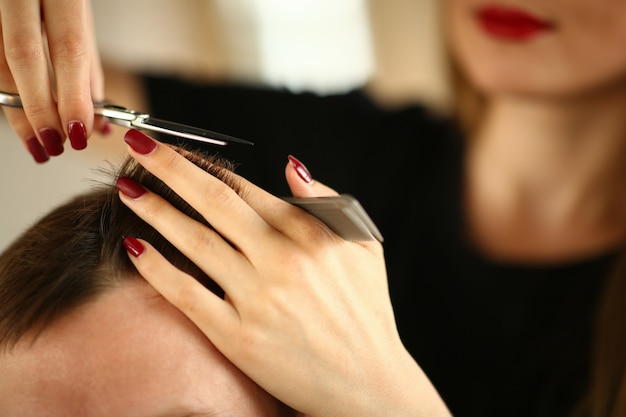 Parrucchiere hands holding scissors e spazzola per capelli