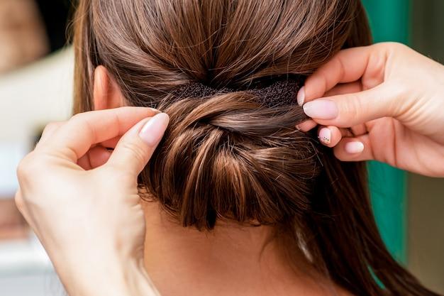 Mani del parrucchiere che fanno acconciatura.