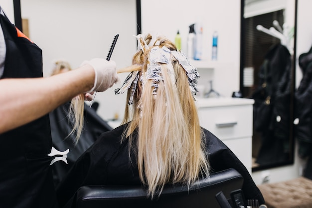 Il parrucchiere sta tingendo i capelli femminili, facendo dei colpi di sole alla sua cliente con una lamina.