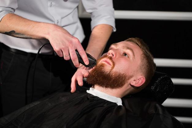 Il parrucchiere sta radendo la barba maschile con il coltello. bell'uomo barbuto si fa rasare dal parrucchiere dal barbiere
