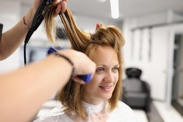 Il parrucchiere fa lo styling dei capelli con asciugacapelli e pettine.