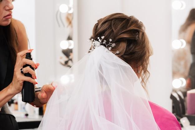 Un parrucchiere fa un'acconciatura elegante per acconciare una sposa con un velo bianco tra i capelli nel salone.