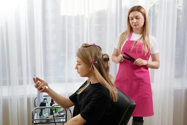 Il parrucchiere fa acconciatura ragazza con i capelli lunghi in un salone di bellezza. crea ricci con arricciacapelli