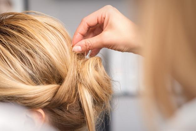 Il parrucchiere fa l'acconciatura della giovane donna