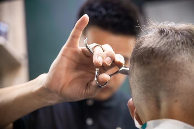 Il parrucchiere fa il taglio di capelli di un uomo. acconciature nei saloni di bellezza