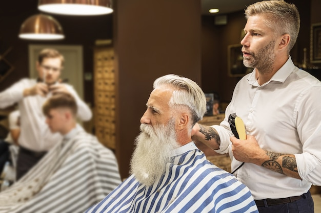 Parrucchiere che fa taglio di capelli alla moda per un bell'uomo anziano nella bottega del barbiere