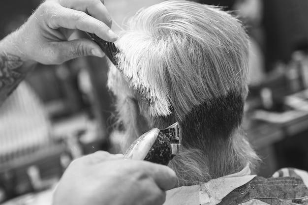 Parrucchiere che fa taglio di capelli alla moda per il vecchio nella bottega del barbiere