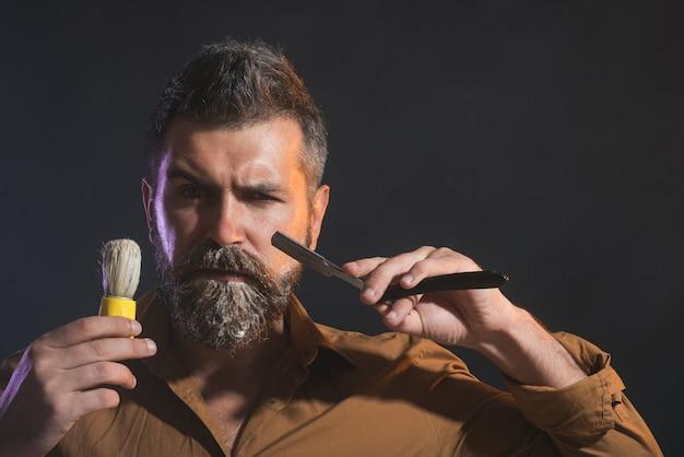 Parrucchiere che posa con l'attrezzatura del barbiere barbiere barbuto serio che dimostra del negozio di barbiere