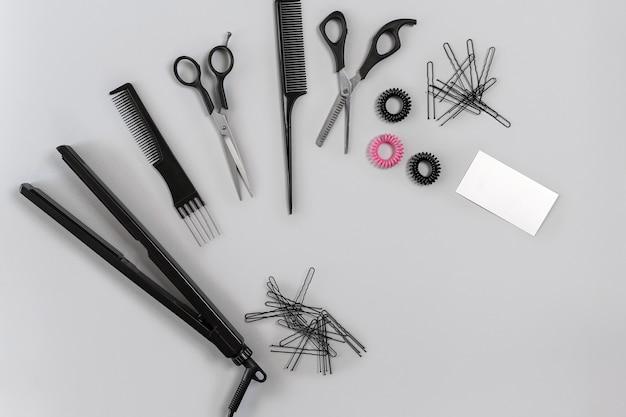 Parrucchiere con vari accessori su sfondo grigio