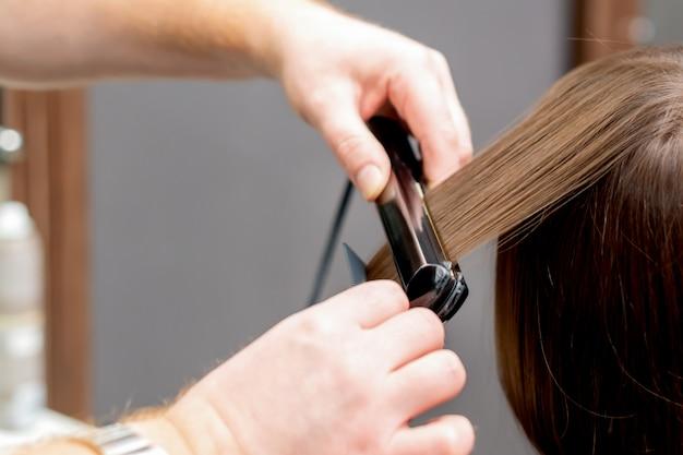 Il parrucchiere raddrizza i capelli della donna.