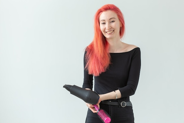 Parrucchiere, stile, concetto di persone - id donna che soffia a secco i suoi capelli colorati.