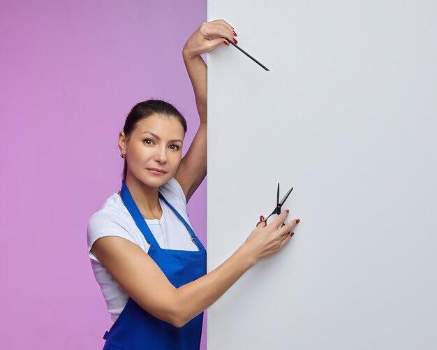 Parrucchiere stilista di aspetto asiatico posa con un cartellone bianco. concetto di pubblicità