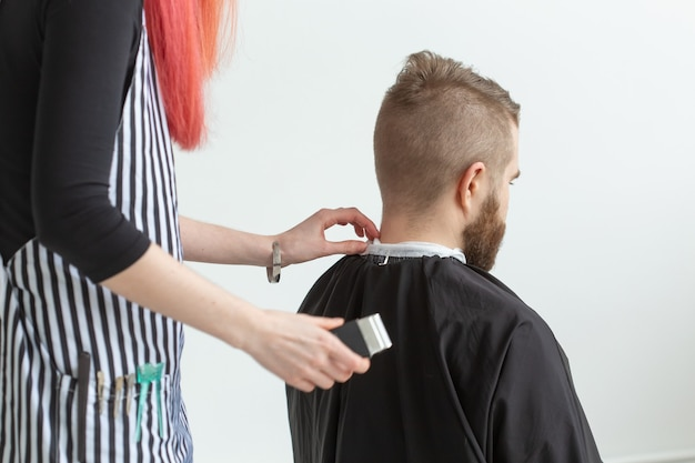 Concetto di negozio di parrucchiere, stilista e barbiere - parrucchiere di giovane donna sta per tagliare i capelli dell'uomo