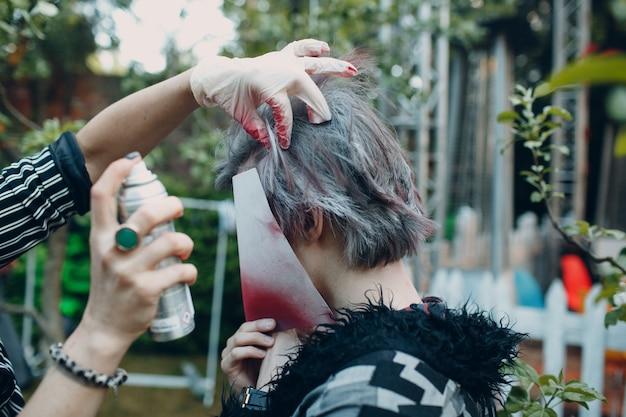 Il truccatore stilista del parrucchiere tinge i capelli di un giovane con una faccia chiusa da una bomboletta spray.
